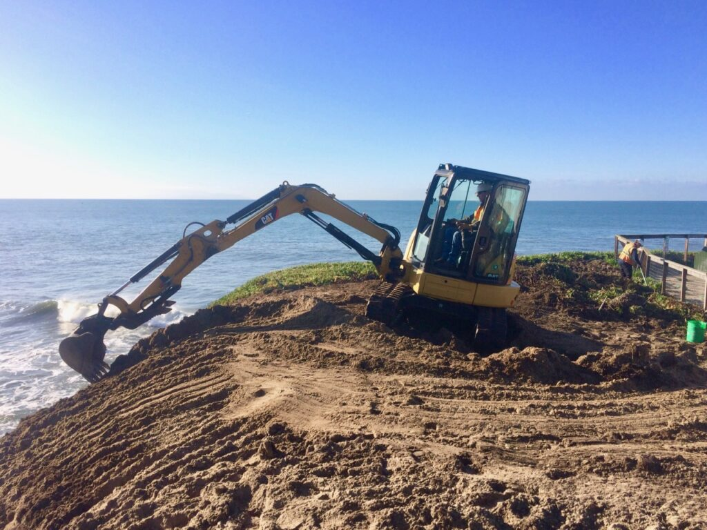 Digger, prepares coastal cliff at natural bridges for planting